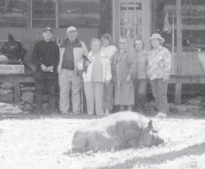 A pig and some of the people who attended the Elk Creek reunion are pictured on the lawn at the log house of Artie Ann Bates.
