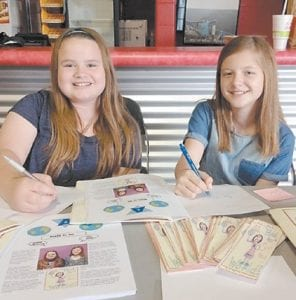Shyann Holbrook (left) and Alex Kincer, sixth-graders at Fleming-Neon Middle School, took part in the second annual Action Research Summit in Pikeville recently as they promoted their book, Al Had to Save the World. The girls co-wrote and illustrated the book last year while they were in Amber Stewart's fifth-grade language arts class at Martha Jane Potter Elementary School. Alex, daughter of Keith and Georgie Kincer, and Shyann, daughter of Marie and Ricky Holbrook, were joined by their parents and other family members as they enjoyed a day of selling and signing their book alongside several other student authors from around the region.