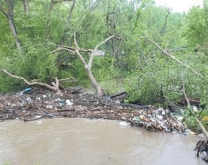LOGJAM — Trash and other debris gathered behind fallen trees and logs to form a dam in the North Fork of the Kentucky River at Mayking, resulting in property losses to two homeowners living between Pine Creek and Cram Creek.
