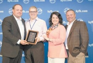 Tony Turner, Kentucky Farm Bureau Insurance Agency support and marketing manager for District Five (left), and Chuck Osborne, KFB Insurance vice president of agency support and marketing (right), present Mark Wright and his wife, Ellena, with the 2015 District Five Agency Manager of the Year award.