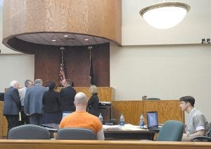 WANT TRIAL MOVED — Accused killers Patrick Smith (wearing orange) and James Huffman (right) sat in Letcher Circuit Court for a hearing June 10 as attorneys gathered before Special Judge Kent Hendrickson. Citing an abundance of pretrial publicity, Smith and Huffman have asked Hendrickson, of Harlan County, to order their trial in the Michael Hogg murder case moved to another county. (Photo by Ben Gish)