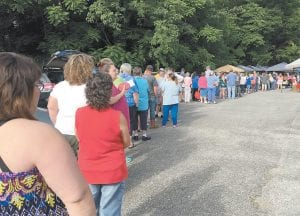 Participants of Mountain Comprehensive Health Corporation's fruit and vegetable voucher program waited in line before the City of Whitesburg/Letcher County Farmers Market opened Saturday morning.