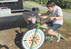 """Kaitlyn Horn, 15, of Winchester, pedaled the """"fender blender"""" Saturday at the Farmers Market. Horn made a fruit smoothie by pedaling a bike to power a blender filled with yogurt, honey and fresh fruit. Children under 18 are served free vegetable wraps and smoothies through the United States Department of Agriculture's Summer Feeding Service Project sponsored by Cowan Community Action Group. The fender blender was donated by Mountain Comprehensive Health Corporation."""