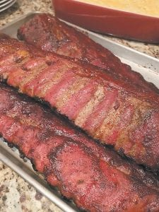 The best way to test for doneness of smoked pork ribs is to make sure that the meat has receded from the end of the bones and that you can bend the rack without breaking it in pieces. The best ribs should be tender but have a little chew left. (Elizabeth Karmel via AP)