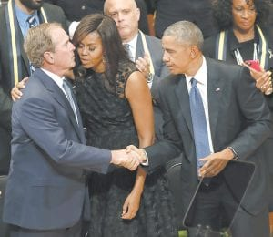 President Barack Obama, left, and first lady Michelle Obama, center, reach out to former President George W. Bush, left during a memorial service at the Morton H. Meyerson Symphony Center with the families of the fallen police officers Tuesday in Dallas. Five police offi cers were killed and several injured during a shooting in downtown Dallas last Thursday night. (AP Photo/Eric Gay)