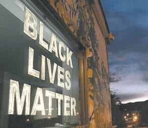 """A """"Black Lives Matter"""" sign attached to a building near Whitesburg's Main Street resulted in a war of words on social media last Friday morning that grew even more heated after it was shown on television news. A """"Blue Lives Matter"""" sign was placed downtown Tuesday on a highway overpass bridge. (Photos courtesy WYMT-TV, Hazard)"""