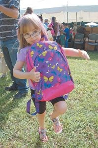 READY FOR SCHOOL — Five-year-old Elizabeth Hall hugs a backpack filled with school supplies she received at the Letcher County Kids Day Back-to-School Bash at River Park in Whitesburg on July 22. The Kids Day committee and the Family Resource and Youth Services Center (FRYSC) provided the backpacks. Elizabeth is the daughter of Tonya and Anthony Hall of Whitesburg. (Photo by Sally Barto)