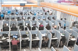 """Workers sitting at desks at a call center. If you spend all day sitting, then you might want to schedule some time for a brisk walk — just make sure you can spare at least an hour. Scientists analyzing data from more than 1 million people found that it takes about 60 to 75 minutes of """"moderate intensity"""" exercise to undo the damage of sitting for at least eight hours a day. Not exercising and sitting all day is as dangerous as being obese or smoking. (AP Photo)"""