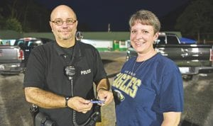 """Rye Cove, Va., football fan Vanessa Wynn, right, presented a bracelet to Jenkins Police Chief Jim Stephens during a pre-season football game on Aug. 12. The bracelet reads """"Blessed are the peacemakers"""" and is part of the """"Matthew 5:9 Project,"""" a Christian-based outreach organization that recognizes the service of police officers to their communities. Wynn approached Stephens after the game, thanked him for his service and gave him the bracelet. (Photo by Chris Anderson)"""