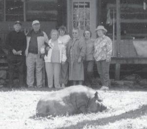 A pig lies on the ground in front of some of the people who attended the Elk Creek reunion in 1999 at the log house of Artie Ann Bates.