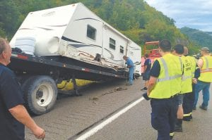 — A wreck in Letcher County last week ruined a planned NASCAR race outing to Tennessee for Kathy and Kelly Jefferson of Prestonsburg. The couple escaped injury in a crash on U.S. 23 near Jenkins, but their camper was heavily damaged. Emergency responders at the scene said Kevin Mullins of Dorton was traveling toward Pikeville when he fell asleep at the wheel of his pickup truck and crossed the center lane. Kelly Jefferson was able to avoid a head-on collision, but Mullins's pickup still hit the family's camper. Mullins was treated at the scene for injuries and released. The Jeffersons and their 12-year-old daughter were on their way to Bristol Motor Speedway for the NASCAR race weekend, but had to abandon their plans and have the camper hauled back home to Floyd County instead. (Photo by Chris Anderson)