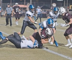 Letcher Central senior Triston Polly, left, and teammate Gage Isaac to bring down the Pikeville ball carrier, while teammates Tyler Boggs, top left, and Leyton Polly, top right, provided support. (Photo by Chris Anderson)