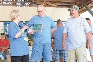 Jenkins Homecoming Days Festival Committee Member Joann Baldwin, left, and Jenkins Mayor Todd Depriest, right, presented a plaque of appreciation to longtime festival emcee and musician Chuck Johnson, who was in his last year as emcee of the festival.