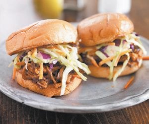 The meat for these crowd-pleasing easy Barbequed Pulled-Pork Sandwiches is prepared in a crockpot.