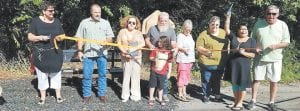 Sherry Spradlin, Lee Ann Colwell Gabbard, Letcher County Magistrates Terry Adams and Keith Adams, Linda Hatton, Berma Matthews, Gwen Rollins, Jim Croucher broke ground for the Little Free Library. At front center is Addison Stonic.
