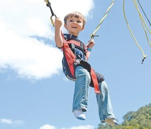 — Braxton Bentley smiles and soars into the sky on the bungee swings at the Isom Days festival on Saturday. (Photo by Chris Anderson)
