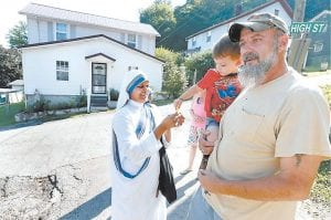 Sister Suma Rani gave a piece of candy to 2-year-old Randon Phillips, held by his grandfather Randall Phillips, who was talking to Sister Dominga outside the Missionaries of Charity convent in Jenkins. In the background, Vicky Philips, Randall's wife and Randon's grandmother, talked to Sister Imeldina. Mother Teresa opened the mission in 1982. (Photo by Charles Bertram, courtesy Lexington Herald-Leader)