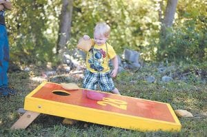 Braylen Reynolds wasn't exactly following the rules of the game of cornhole at the Isom fairgrounds, but no one seemed mind as he had a blast dropping bean bags through the board prior to the start of Isom Days Cornhole Tournament. (Photo by Chris Anderson)