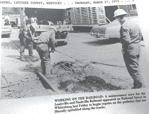 This image is taken from the March 27, 1975 edition of The Mountain Eagle and shows an L&N Railroad repair crew working to fix potholes in downtown Whitesburg less than 24 hours after Helen Bentley blocked the railroad tracks with her small car and refused to move it unless the railroad agreed to fix the badly damaged street.