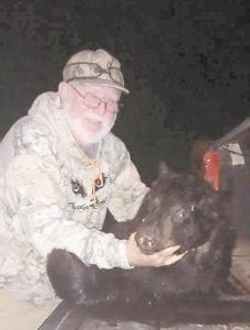 Columnist Steve Brewer poses with a black bear he killed in Maine recently — his final hunt in the Pine Tree State.