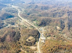 This photograph taken from a small airplane shows the Mayking area of Letcher County with U.S. Highway 119 splitting it in the middle. The buildings shown near the bottom of photo show the Mayking Mall area. At left is the old Mayking golf course area. Buildings housing the county and state highway garages are in the top left portion of the photo, along with the Ermine Double Kwik. (Mountain Eagle photo courtesy Hazard attorney Doug Holliday and Friendship Flying Service)