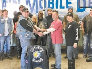Seventh Sons Motorcycle Club (SSMC) sponsored a benefit ride for the community action group, Hands of Hope, a SmileFaith ministry on November 5. Pictured are Kevin Boggs, vice president of SSMC, and Mark and Joanna Hardin, Hands of Hope and SmileFaith representatives, along with ride participants in front of the Mountain Mobile Dental Bus at the SmileFaith Wellness and Community Center in Jenkins.