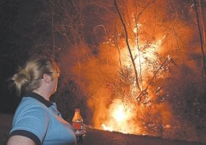 A resident of Premier Subdivision at Jenkins watched flames from a wildfire. (Photo by Chris Anderson)