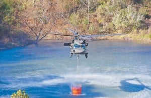 A Kentucky National Guard UH-60 Blackhawk helicopter dipped water out of a sediment pond along U.S. 23 at what used to be the head of Cane Branch of Jenkins on Sunday during airdrop operations to fight the forest fires around the city. (Photo by Chris Anderson)