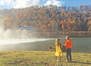 Allison and Christopher Anderson watched as a Columbia Helicopter's CH-47D Chinook prepares to pump water from Jenkins Lake last week. The helicopter was one of three pulling water from area sources to dump onto wildfires burning on Pine Mountain overlooking Jenkins. The aerial operations drew a large crowd of spectators in Jenkins and other areas. (Photo by Debbie Anderson)