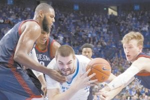 Kentucky's Isaac Humphries, center, was pressured by Duquesne's Darius Lewis, left, and Spencer Littleson during the second half of their game in Lexington Sunday. Kentucky won 93-59. (AP Photo/