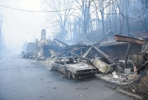 A structure and vehicle are damaged from the wildfires around Gatlinburg, Tenn., on Tuesday. (Knoxville News Sentinel via AP)