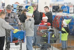 """— Cadets Taylor Hall and Brandon Boggs (back) assisted troopers from Kentucky State Police Post 13 during the post's annual """"Shop With A Trooper"""" event held annually at the Whitesburg Walmart. Gifts purchased included clothes, shoes and socks. This photo by LCC's JROTC instructor, Sgt. Michael Sexton."""