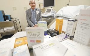 """SEX DRUG PRICE HIKES — Dr. Irwin Goldstein poses in his office in San Diego behind a display of medicine for impotence and for sexual problems. For couples who can't afford the soaring prices for the prescriptions, some take a big risk, buying """"herbal Viagra"""" at gas stations or ordering Viagra online from """"Canadian pharmacies"""" that likely sell counterfeit drugs made in poor countries, says Goldstein, director of San Diego Sexual Medicine. (AP Photo)"""