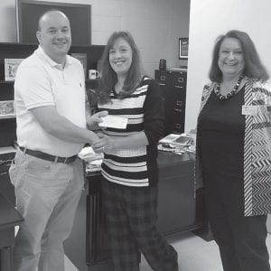 Presenting Jenkins Middle School teacher Brian Bentley (left) with a check for $3,000 from the United Way are (center) Rose Shields of United Way and Abbie Combs of Kentucky Valley Education Cooperative. The money will be used to buy Chrome Books for his class.