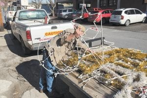 — Lanny Day chose from among several new ornaments recently in downtown Whitesburg as he and others put up Christmas decorations for the city. The new decorations, purchased with funds generated by a city tax on alcohol sales, are drawing praise from many citizens, including a couple of callers who commented favorably in this week's edition of Speak Your Piece. (Eagle photo)