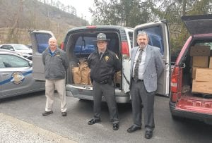 """— Mountain Comprehensive Health Corporation CEO Mike Caudill, right, Kentucky State Police Trooper Jody Sims, center, and former KSP Trooper Tony Watts, left, stood in front of part of a 3-ton collection of non-perishable food items collected here for the KSP's annual """"Cram the Crusier"""" food drive. MCHC has long been a top supporter of the drive and was joined this year by the Isom IGA food store, which agreed to match the food total collected at MCHC. The collected food was immediately delivered on December 14 to food pantries in Fleming-Neon, Jenkins, and Whitesburg. Additional photos inside."""