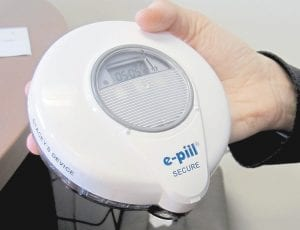 University of Vermont Psychologist Stacey Sigmon holds a tamper-proof electronic pill dispenser in her office in Burlington, Vermont. People hooked on prescription painkillers were able to use the device to take a drug at home to curb cravings and prevent abuse while waiting to get in a treatment program. Use of the device showed dramatic results in helping people who use the system remain free of illicit opioids. (AP Photo)