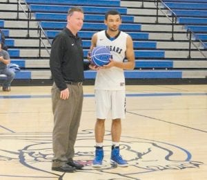 2,000-POINT CLUB — Letcher County Central High School head basketball coach Robert Hammonds presented star player Torrell Carter with a special basketball after Carter scored his 2,000th point.