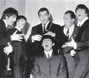 American speed skating champion Terry McDermott, top center, a barber by trade, prepared to take a swipe at the famed locks of Beatle Paul McCartney, seated, to the mock horror of the other Beatles and TV host Ed Sullivan, during rehearsals at the TV Studio, New York, February 9, 1964. From left, George Harrison, Ringo Starr, McDermott, Ed Sullivan and John Lennon. (AP Photo)