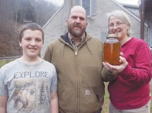 Reuben, Seth and Sheryl Long hold up a jar of their maple syrup. The family expects 20-25 gallons of syrup this year from 75 trees, and hopes to eventually have 500 maple trees tapped. (Photo by Sam Adams)