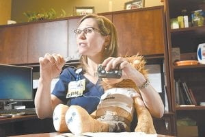 Diabetes educator Kimberly P. Miller, BSN, RN, CDE, holds a Medtronic Minimed diabetes insulin pump in her office at CHI Memorial, in Chattanooga, Tenn. (Chattanooga Times Free Press via AP)
