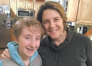"""In this photo provided by Clare Schexnyder, small business owner Clare Schexnyder, 49, poses with her daughter, Sofi, in their kitchen in Decatur, Georgia. A breast cancer survivor, Schexnyder says she wouldn't be alive if not for the Obamacare that paid for her mammograms, and finds it """"unforgiveable"""" that Republicans are sabotaging access to affordable health care. (AP Photos)"""