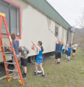 COMMUNITY SERVICE — The Letcher County Central JROTC Raider Team participated in a community service project at the Summit Community Children's Church Building March 30. The team is pictured painting the church building. (Photo by Damaris Sexton)