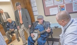 """PERFORMING FOR CLINIC VISITOR — Old-time banjo picker Lee Sexton performs for former U.S. Rep. Ben Chandler (in orange tie), now the president and CEO of Foundation for a Healthy Kentucky, during Chandler's visit to Mountain Comprehensive Health Corporation's Leatherwood Clinic. Also watching Sexton perform were MCHC CEO L.M. """"Mike"""" Caudill (far left) and Dr. Van Breeding (far right). Seated near left is Ralph Hall, who performed an old hymn in the a cappella style. (Photo by Malcom Wilson)"""