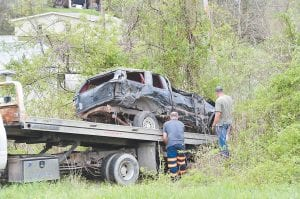 SCENE OF FATAL WRECK — Workers are seen loading the 1994 Ford Explorer that was being driven by 28-year-old Larry C. Stidham when it crashed near the Payne Gap entrance to Bottom Fork early Sunday morning. Stidham had been expected to testify in the trial of James Huffman IV, but the case was ordered postponed by Special Letcher Circuit Judge Kent Hendrickson. (Photo by Chris Anderson)