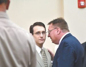 TRIAL DELAYED — James Huffman IV (center) spoke with attorney Robert Wright after Huffman's trial in connection with the murder of Michael Hogg was postponed this week in Letcher Circuit Court. (Photo by Chris Anderson)