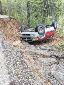 Above, a vehicle belonging to Kathy and Mark Miles of Big Cowan overturned after the road leading to their home was destroyed by a slide during heavy rains over the weekend. Below, Letcher County Judge/Executive Jim Ward finished clearing a culvert that had blocked water and flooded Craft's Colly Road at Angel Road.