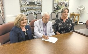 Mayor James W. Craft signs documents as state Local Government Commissioner Sandy Dunahoo and KRADD Program Director Annette Napier look on.