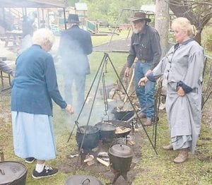 Cooking over an open fire was demonstrated at the first session of the Back to Our Appalachian Roots program held May 6 at the Hemphill Community Center. Pictured (left to right) are Mabel Johnson, George Gibson, Greg Bentley and Gemma Bentley.