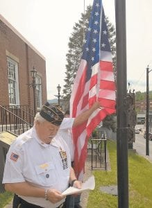 Darrell Holbrook reads a patriotic story about the American flag while Wayne Watts and Buddy Grubb replace the tattered flag in front of the old post office building in Whitesburg last week. Holbrook and Watts, both of Whitesburg, are members of Disabled American Veterans Chapter 171 in Knott County. Grubb runs the Letcher County Veterans Memorial Museum in Whitesburg. The flag was replaced at the request of Trey Sexton, who owns a solar installation company in the building.